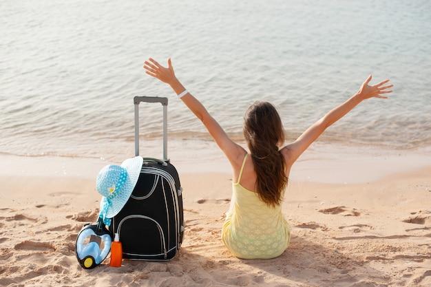 Wakacje na plaży kobieta ciesząc się letnim słońcem siedząc w piasku patrząc szczęśliwy