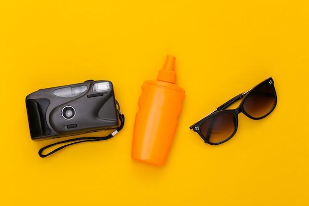 Wakacje na plaży, koncepcja podróży. butelka z filtrem przeciwsłonecznym, okulary przeciwsłoneczne i aparat na żółto