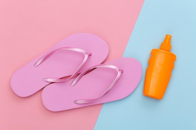 Wakacje na plaży. lato. butelka z filtrem przeciwsłonecznym i klapki na różowym niebieskim pastelu