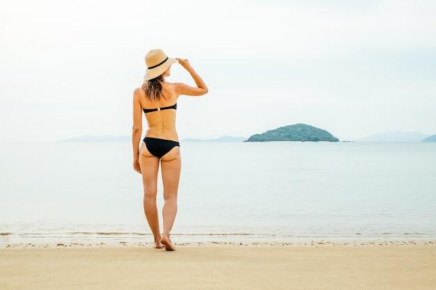 Wakacje na plaży. piękna kobieta w kapeluszu i bikini stojąc na plaży, ciesząc się, patrząc widok na ocean w letni dzień