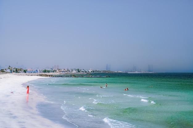 Wakacje na plaży tło. dubai. zatoka perska z linią plaży od ajman. kobieta w czerwieni bawić się na plaży.