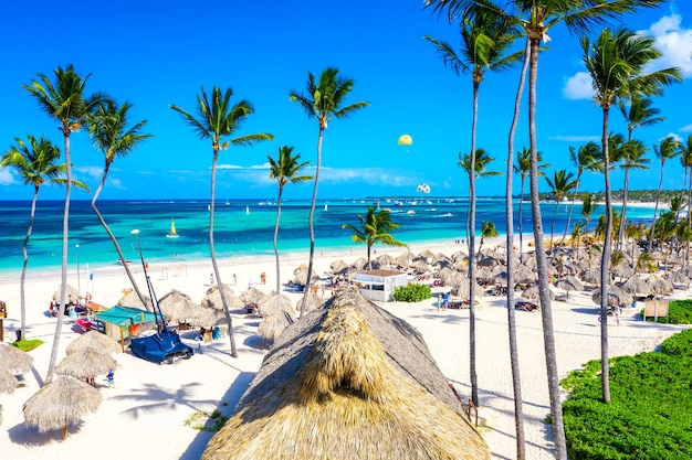 Wakacje na plaży. widok z lotu ptaka drona tropikalnej białej piaszczystej plaży bavaro w punta cana, dominikana. niesamowity krajobraz z palmami, parasolami i turkusową wodą oceanu atlantyckiego.
