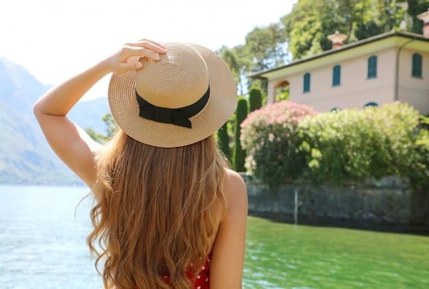 Wakacje nad jeziorem como. widok z tyłu podróży turystycznych dziewczyna relaksujący widok na krajobraz jeziora como z miasta bellagio we włoszech.
