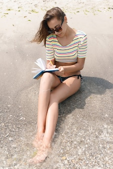 Wakacje, ośrodek, koncepcja turystyki - kobieta robi notatki i siedzi na plaży. kobieta pisze w pamiętniku i leży na piasku