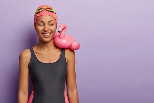Wakacje, plaża, koncepcja lato. uśmiechnięta ciemnoskóra kobieta przygotowuje się do przyjęcia na basenie, nosi czarny kostium kąpielowy, okulary ochronne