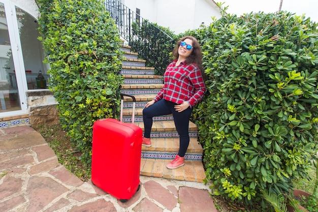 Wakacje, podróże, koncepcja ludzi - młoda kobieta w okularach przeciwsłonecznych stojących na schodach z walizkami i uśmiechnięta