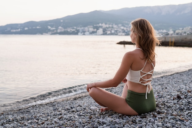 Wakacje. pojęcie zdrowia. piękna młoda kobieta w stroju kąpielowym medytująca na plaży