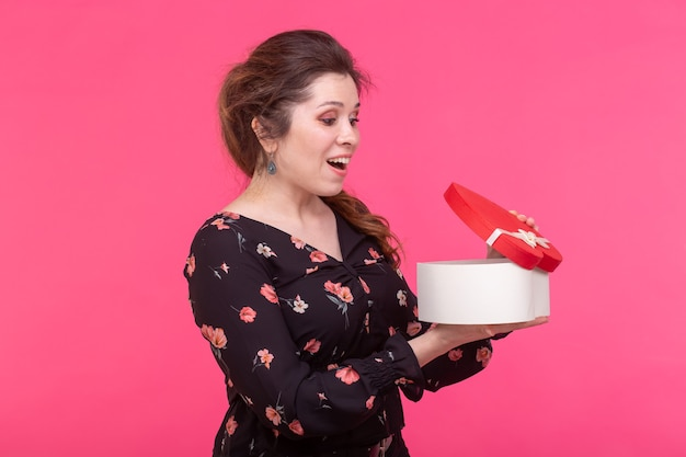 Wakacje, prezent i niespodzianka koncepcja - piękna szczęśliwa dziewczyna z pudełkiem na prezent valentine na różowo