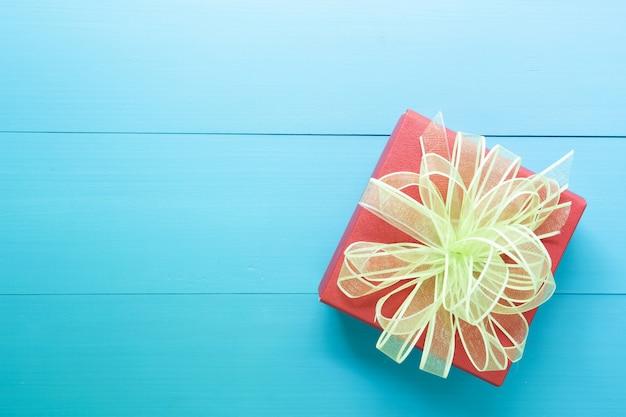 Wakacje pudełko z kokardą na drewnianym niebieskim stole, prezent romantyczny dzień na drewnie