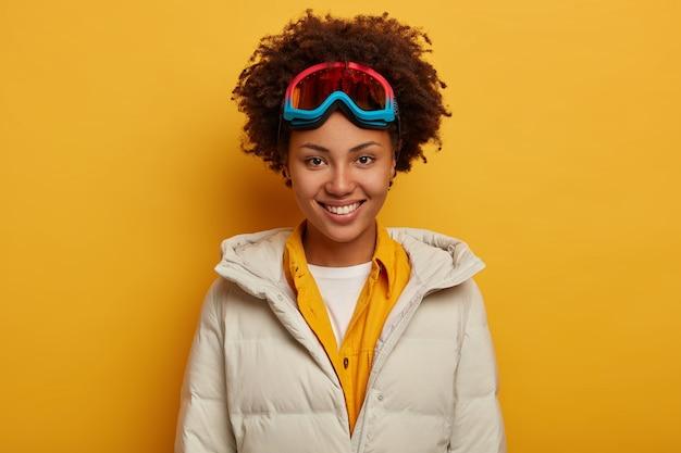 Wakacje sportowe, styl życia w podróży i koncepcja przygody zimowej. uradowana afrykańska kobieta z zębowatym uśmiechem, snowboardy w górach, gogle narciarskie i biały puchowy płaszcz