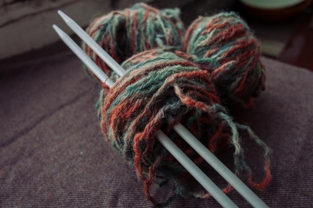 Wakacje, styl życia, koncepcja hobby - kulka fotograficzna przędzy z igłami do robienia na drutach. clews z kolorowej przędzy wełnianej. zdjęcie z bliska