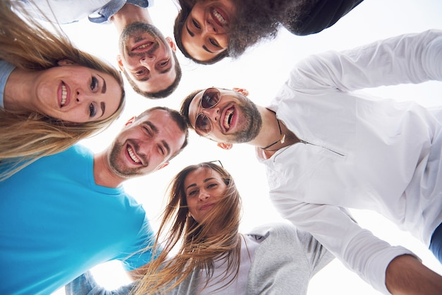 Wakacje, szczęśliwi ludzie - grupa nastolatków spoglądających w dół ze szczęśliwym uśmiechem na twarzy.