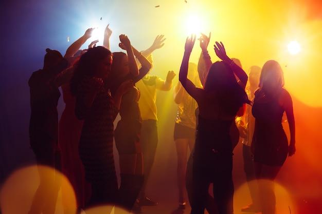 Wakacje. tłum ludzi w sylwetce podnosi ręce na parkiecie na neonowym tle. życie nocne, klub, muzyka, taniec, ruch, młodzież. żółto-niebieskie kolory i poruszające dziewczyny i chłopcy.