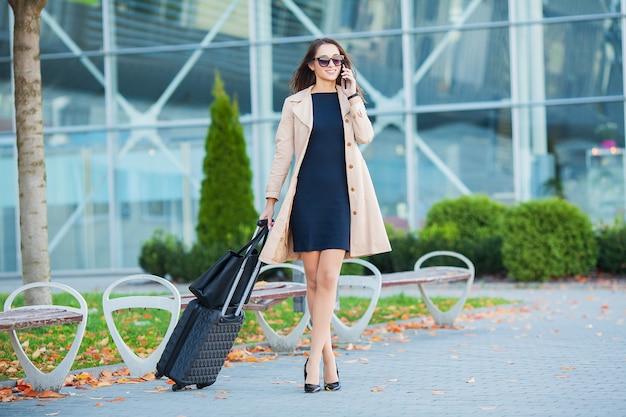 Wakacje. uśmiechnięty żeński pasażer przystępuje do wyjścia bramy ciągnąc walizkę przez hali lotniska