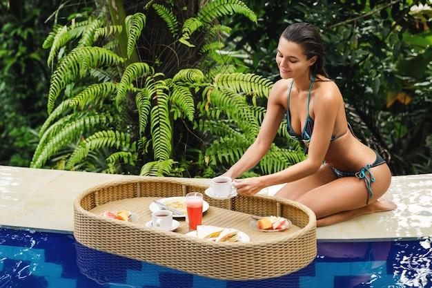 Wakacje w ośrodku. młoda szczęśliwa kobieta z pływającym śniadaniem w basenie.