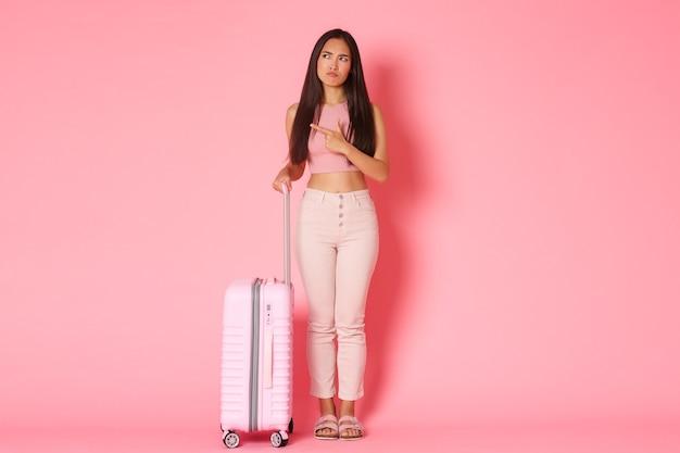 Wakacje w podróży i koncepcja wakacji pełna długość niezdecydowanej i niezadowolonej azjatyckiej turystki ...