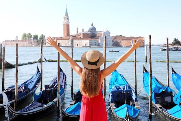 Wakacje w wenecji. widok z tyłu pięknej dziewczyny z podniesionymi rękami do góry, ciesząc się widokiem na lagunę wenecką z wyspą san giorgio maggiore i zacumowanymi gondolami.