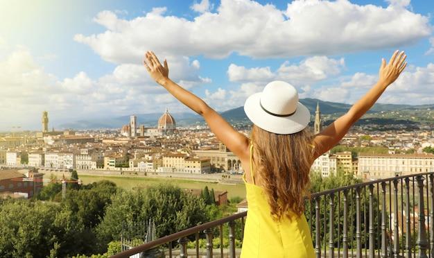 Wakacje we włoszech. panoramiczny widok z tyłu młodej kobiety w kapeluszu i podniesionymi rękami, patrząc na miasto florencja, toskania, włochy.
