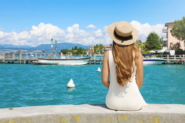 Wakacje we włoszech. widok z tyłu piękna dziewczyna siedzi na ścianie z widokiem na port sirmione nad jeziorem garda. letnie wakacje we włoszech.