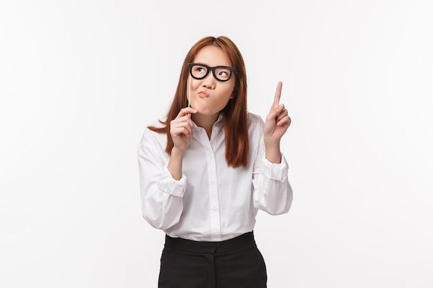 Wakacje, życie biurowe i koncepcja kobiet. portret rozważnego śmiesznego azjatykciego żeńskiego przedsiębiorcy trzyma szkła na kij masce i bielmikuje podczas gdy myśleć, odwraca wzrok podnosi palec na eureka gescie