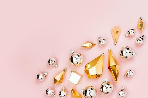 Wakacyjna aranżacja z stylowymi bożonarodzeniowymi błyszczącymi kulkami i złotymi kryształkami na pastelowym różowym tle. płaski układanie, widok z góry