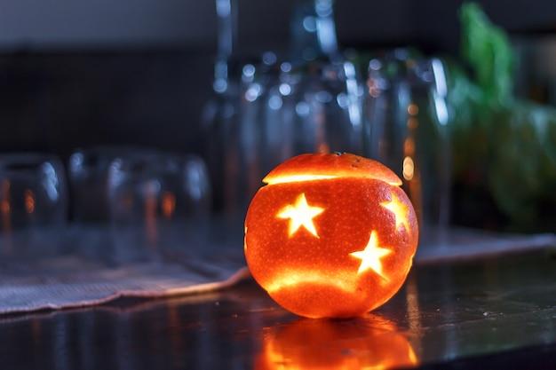 Wakacyjna pomarańcza na ciemnym stole ze światłem.