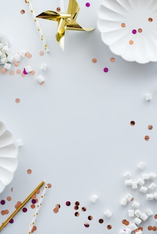 Wakacyjna rama lub tło z kolorowymi błyskotkami, konfetti, złotą gwiazdą, ptasie mleczko, białe talerze, patyczki. płaski układ. kartkę z życzeniami urodzinowymi lub party z miejsca kopiowania.