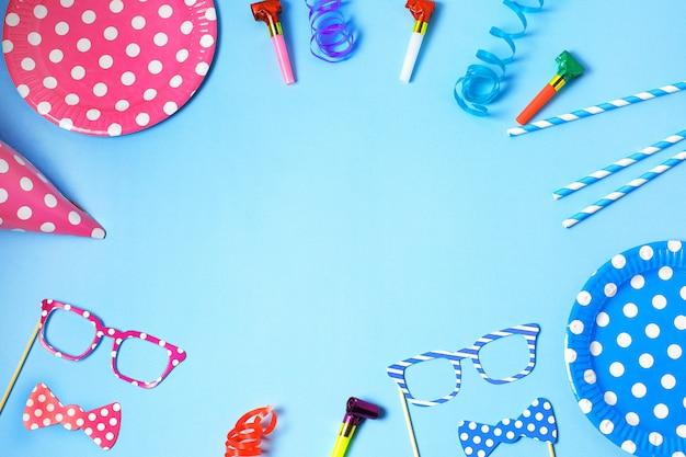Wakacyjna rama lub tło z papierowymi naczyniami i słomkami, rogami, śmiesznymi okularami, karnawałową czapką i chorągiewką