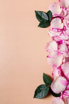 Wakacyjna ramka wykonana z jasnoróżowych płatków róż na tle pastelowego tła, kartki z życzeniami walentynkowymi lub ślubnymi