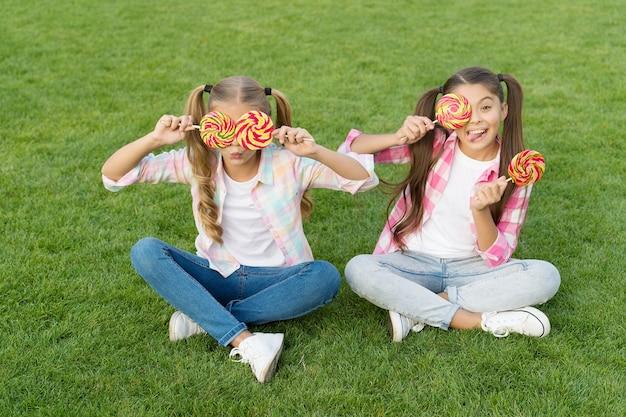 Wakacyjne jedzenie. słodkie dzieciństwo. szczęśliwe dzieci posiadają cukierki siedzą na zielonej trawie. sklep ze słodyczami. lizaki przysmaki. cukierkowy synonim szczęścia. cukier i kalorie. radosny wesoły przyjaciele jedzenie słodyczy na świeżym powietrzu.