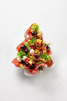Wakacyjne kanapki w talerzu w kształcie choinki na świąteczne przyjęcie bożonarodzeniowe na białym stole. widok z góry. format pionowy.