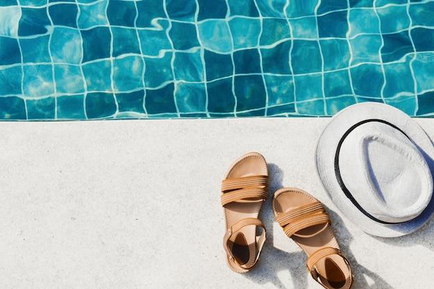 Wakacyjne mieszkanie leżało w damskich sandałach i czapce przed basenem