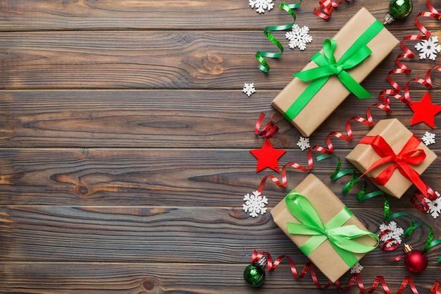 Wakacyjne mieszkanie leżało z pudełkami prezentowymi zawiniętymi w kolorowy papier i przewiązanymi ozdobionymi konfetti na kolorowym tle. boże narodzenie, urodziny, walentynki i koncepcja sprzedaży, widok z góry