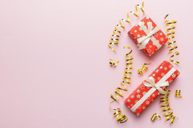 Wakacyjne mieszkanie leżało z pudełkami prezentowymi zawiniętymi w kolorowy papier i przewiązanymi ozdobionymi konfetti na kolorowym tle. boże narodzenie, urodziny, walentynki i koncepcja sprzedaży, widok z góry.