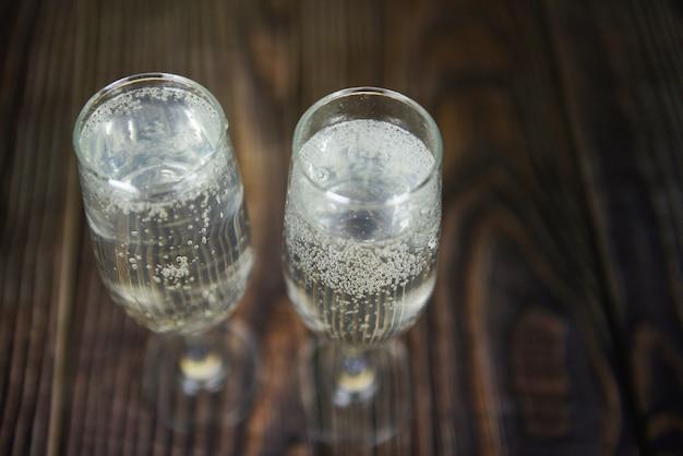 Wakacyjne napoje ze szkła prosecco, takie jak przyjęcie tematyczne i święto z kieliszkami do szampana na zimowe wakacje, udekorowane bożonarodzeniowymi na drewnianym stole