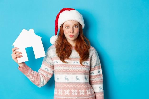 Wakacyjne promocje i koncepcja nieruchomości. śliczna ruda kobieta w czapce i swetrze świętego mikołaja przedstawiająca papierowy model domu, ofertę mieszkania, stojąca na niebieskim tle.