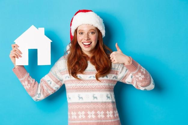 Wakacyjne promocje i koncepcja nieruchomości. zadowolona modelka z czerwonymi falującymi włosami, ubrana w czapkę mikołaja i sweter, pokazująca modelkę papierowego domu i kciuki do góry, niebieskie tło.