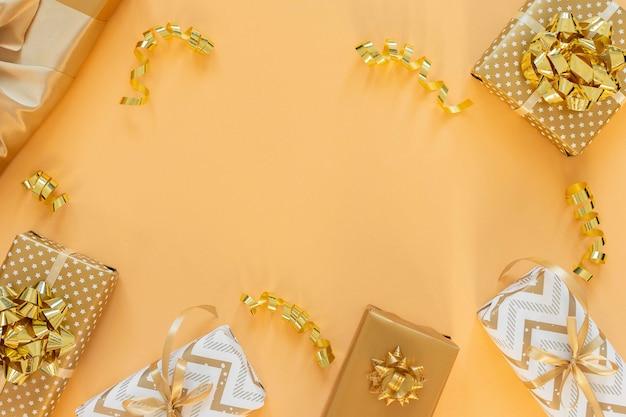 Wakacyjne tło w złotych kolorach, pudełka na prezenty z błyszczącymi kokardkami i brokatowymi wstążkami serpentynami na złotym tle, płaskie ułożenie, widok z góry, kopia przestrzeń