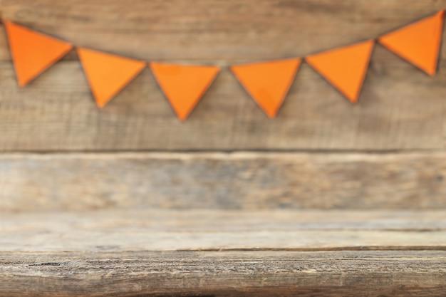 Wakacyjne tło z niewyraźną girlandą pomarańczowych flag skoncentruj się na pierwszym planie