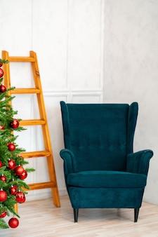 Wakacyjne wnętrze. pięknie zdobiona choinka z niebieskim fotelem