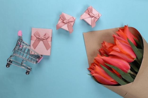 Wakacyjne zakupy. bukiet czerwonych tulipanów, pudełka na prezenty, wózek w supermarkecie na niebiesko