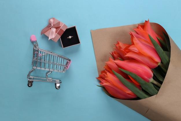 Wakacyjne zakupy. bukiet tulipanów, złoty pierścionek z diamentem w pudełku prezentowym, wózek do supermarketu na niebiesko