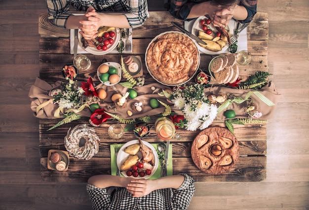 Wakacyjni przyjaciele lub rodzina przy świątecznym blatem. przyjaciele modlą się na cześć wielkanocy przy świątecznym stole
