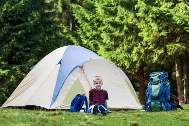 Wakacyjny camping. szczęśliwy młody chłopiec siedzi przed namiotem blisko plecaków odpoczywa po wycieczkować w lesie.
