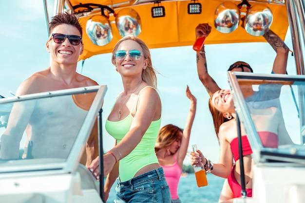 Wakacyjny krążownik. uśmiechnięta młoda para stojąca za kierownicą łodzi rekreacyjnej z tańczącymi przyjaciółmi w tle