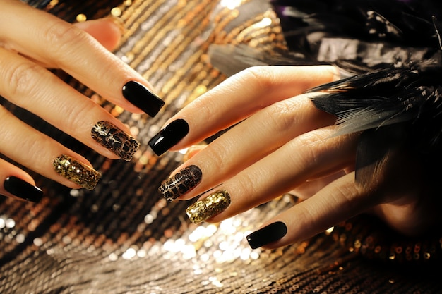 Wakacyjny manicure na długich kwadratowych paznokciach ze złotymi cekinami, czarnym błyszczącym lakierem i craquelure matową czarną powłoką.