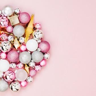 Wakacyjny okrągły układ ze stylowymi świątecznymi błyszczącymi kulkami i złotymi kryształami na pastelowym różowym tle. płaski układanie, widok z góry