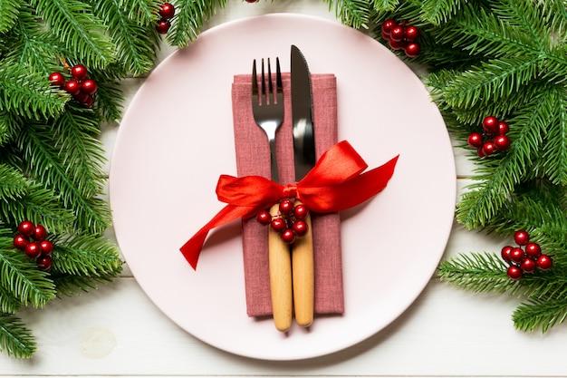 Wakacyjny skład talerz i sztućce dekorował z jedlinowym drzewem na drewnianym tle
