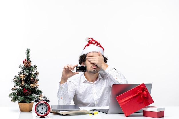 Wakacyjny świąteczny nastrój z młodym zmęczonym biznesmenem w kapeluszu świętego mikołaja i trzymając swoją kartę bankową w biurze na białym tle