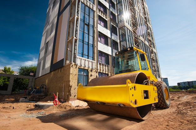 Wał ciągnika zagęszcza ziemię w nowym domu w budowie